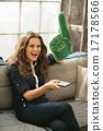 Portrait of happy football fan woman watching tv in loft apartme 17178566