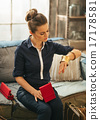 Young woman with shopping bags trying jewelry in loft apartment 17178581