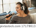 Portrait of young woman singing with microphone in loft apartmen 17178613