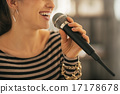 Closeup on happy young woman singing with microphone 17178678