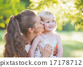 Portrait of mother kissing baby outdoors 17178712