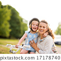 Proud girl on a bicycle hugging her mother in a city park 17178740