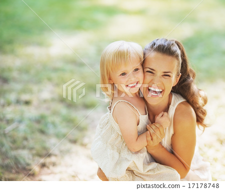 Portrait of smiling mother and baby outdoors 17178748
