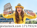 Young woman showing thumbs up in front of colosseum in rome, ita 17179324