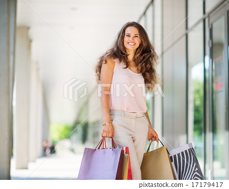 Stock Photo: Brown-haired woman smiling about her successful shopping spree