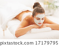 Relaxed young woman with revitalising mask on face laying on mas 17179795