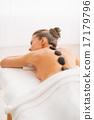 Young woman receiving hot stone massage. rear view 17179796