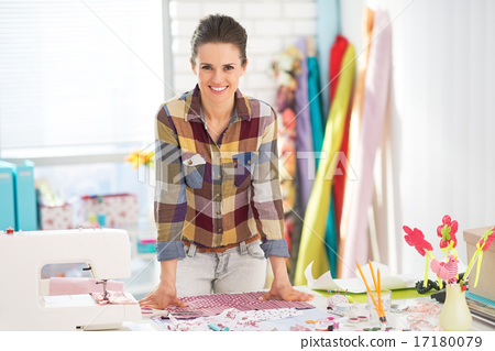 Portrait of happy seamstress in studio 17180079
