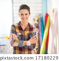 Portrait of happy seamstress with scissors and measuring tape 17180229