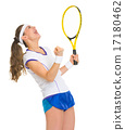 Happy female tennis player with racket rejoicing success 17180462