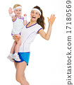 Smiling mother and baby in tennis clothes greeting 17180569