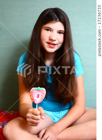 preteen beautiful girl with strawberry candy on stick 17236735