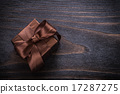 Boxed present with brown bows on vintage wood board 17287275