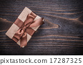 Gift box with brown tied bow on vintage wooden board 17287325