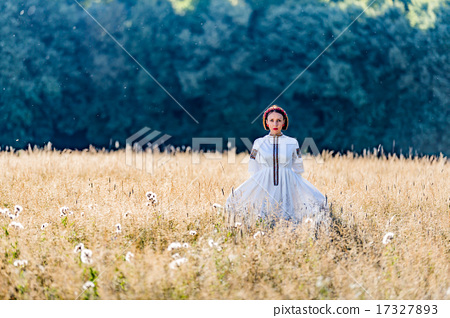 Girl dressed in traditional ethnic costume stands on a background of forest  17327893