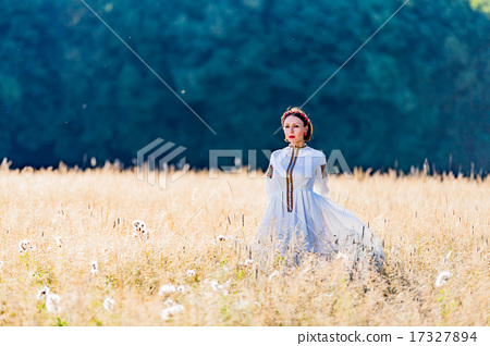 Girl dressed in traditional ethnic costume stands on a background of forest  17327894