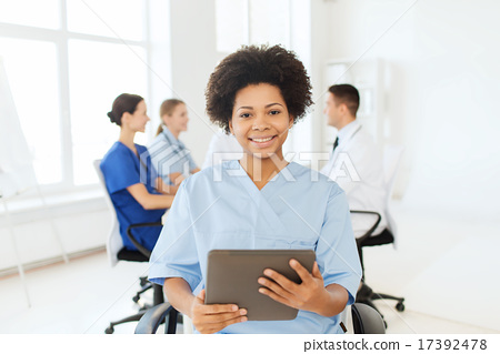 Stock Photo: happy nurse with tablet pc over team at hospital