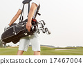 Man carrying his golf bag across course 17467004