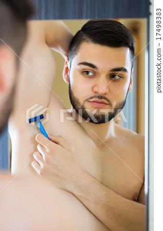 Man shaving armpit hair 17498383