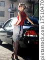blonde woman near black automobile 17510470