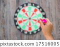 Hand holdin red arrow and throwing to dart board 17516005