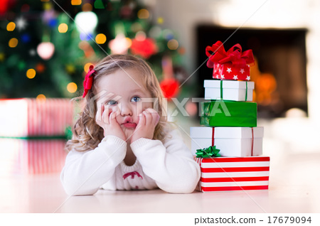 Stock Photo: Little girl opening Christmas presents at fire place
