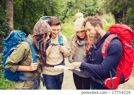 Stock Photo: group of smiling friends with backpacks hiking
