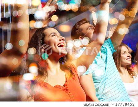 Stock Photo: smiling friends at concert in club