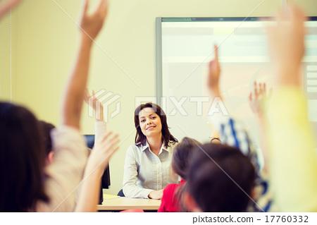 Stock Photo: group of school kids raising hands in classroom