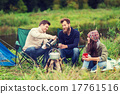 group of smiling tourists cooking food in camping 17761516