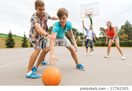 Stock Photo: group of happy teenagers playing basketball