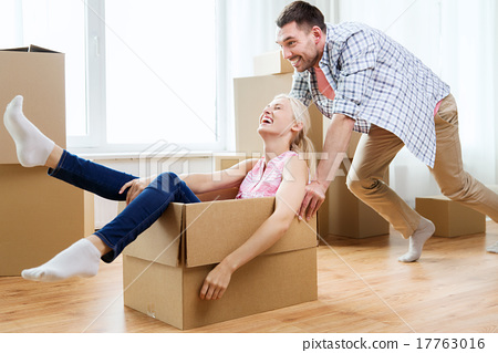 Stock Photo: couple with cardboard boxes having fun at new home