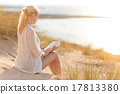 Woman enjoys reading on beautiful sandy beach. 17813380