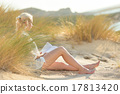 Woman enjoys reading on beautiful sandy beach. 17813420
