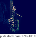 Closeup saxophone in player action on a dark background, dark bl 17824019
