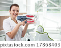 Attractive female dental doctor is carrying 17868403