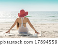 One Asian woman sitting on the beach with red hat 17894559