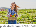 Young woman holding wooden crate with vegetables 17916740