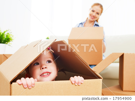 Stock Photo: happy family moves into a new apartment. happy baby in a cardboa