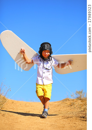 kid with wings and flying helmet plays in the 17989323