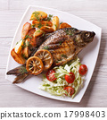 grilled fish with potatoes and salad top view 17998403