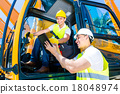 Asian construction driver discussing with engineer blueprints 18048974