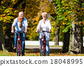 Seniors on bicycles having tour in park 18048995