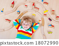 Little blond child playing with wooden railroad trains indoor 18072990