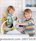 Funny twin boys helping in kitchen with washing dishes 18073038