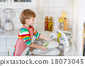 Happy little blond kid boy washing dishes in domestic kitchen 18073045