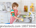 Funny blond kid boy washing dishes in domestic kitchen 18073046