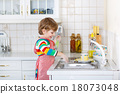 Happy little blond kid boy washing dishes in domestic kitchen 18073048