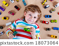 Adorable cute child with lot of different colorful toy cars 18073064