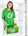 Smiling eco-minded brunette holding recycling bottles 18115199